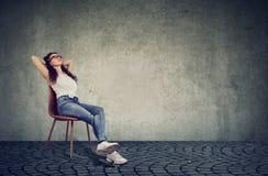 Avkopplad kvinna som vilar på stol royaltyfri fotografi