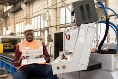 Avkopplad läs- tidning för maskinoperatör royaltyfri fotografi