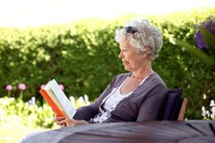 Avkopplad läsebok för äldre kvinna Arkivbilder