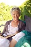 Avkopplad läsning för gammal kvinna i trädgård Royaltyfri Bild