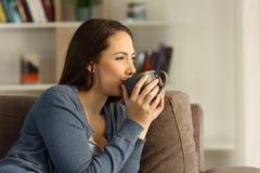 Avkopplad lycklig kvinna som hemma dricker kaffe royaltyfria bilder