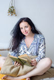 Avkopplad lycklig kvinna som hemma läser ett boksammanträde på en soffa royaltyfri fotografi