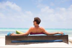 Avkopplad man i den lyxiga dagdrivaren som tycker om sommarsemestrar på den härliga stranden Arkivbild