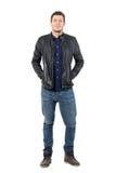 Avkopplad man i jeans och läderomslag som ler på kameran med händer i fack arkivfoto