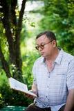 Avkopplad man som sitter, i park och att läsa Royaltyfria Foton