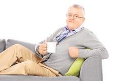 Avkopplad mogen man som lägger på soffan och dricker te Royaltyfri Foto