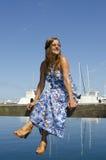 Avkopplad och lycklig kvinna som sitter på marinaen Royaltyfri Fotografi