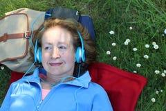 Avkopplad pensionär som lyssnar till musik i natur arkivfoto
