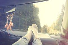 Avkopplad person med fot på instrumentbrädan under biltur royaltyfria bilder