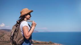 Avkopplad ryggsäckkvinna för Hipster som beundrar fantastiskt seascapeanseende på maximum av berget stock video
