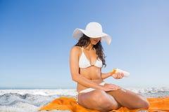 Avkopplad sexig kvinna som applicerar solkräm, medan sitta på hennes handduk royaltyfria foton