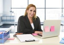 Avkopplad 40-talkvinna med blont hår som ler säkert sammanträde på kontorsstol som arbetar på bärbar datordatoren Arkivfoto