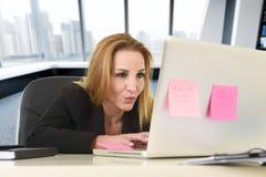 Avkopplad 40-talkvinna med blont hår som ler säkert sammanträde på kontorsstol som arbetar på bärbar datordatoren Arkivbilder