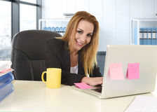 Avkopplad 40-talkvinna med blont hår som ler säkert sammanträde på kontorsstol som arbetar på bärbar datordatoren Royaltyfri Fotografi