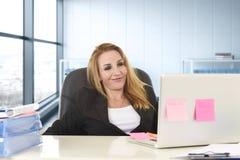 Avkopplad 40-talkvinna med blont hår som ler säkert sammanträde på kontorsstol som arbetar på bärbar datordatoren Royaltyfri Bild