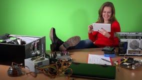 Avkopplad teknikerkvinna med ben på tabellen som spelar med minnestavlan arkivfilmer