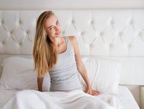 Avkopplad tonårig flicka, kvinna efter sömn på säng i hennes hus, feriesemesterbegrepp arkivfoto
