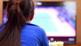 Avkopplad tonårs- flicka med fjärrkontroll som håller ögonen på smart TV arkivfilmer