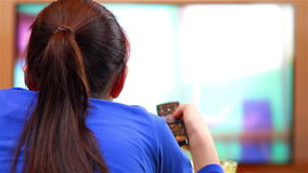 Avkopplad tonårs- flicka med hållande ögonen på tecknade filmer för fjärrkontroll lager videofilmer