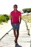 Avkopplad ung afrikansk man som utomhus går Arkivfoton
