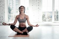 Avkopplad ung dam i hörlurar som bara mediterar Arkivbild