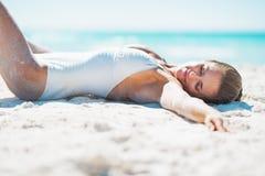 Avkopplad ung kvinna i baddräkt som solbadar på den sandiga stranden Royaltyfri Foto
