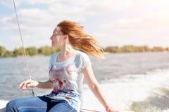 Avkopplad ung kvinna med stängda ögon av nöje som sitter på segelbåten som tycker om mild solljus-, havs- eller flodkryssning, so arkivbilder
