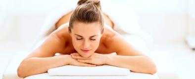 Avkopplad ung kvinna som lägger på massagetabellen royaltyfria foton