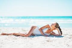 Avkopplad ung kvinna som lägger på stranden arkivbild