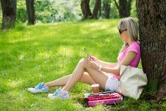 Avkopplad ung kvinna som utomhus använder minnestavladatoren Arkivbilder