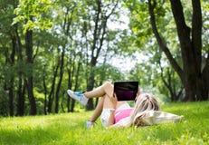 Avkopplad ung kvinna som utomhus använder minnestavladatoren Royaltyfri Foto