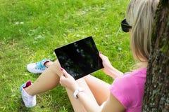 Avkopplad ung kvinna som utomhus använder minnestavladatoren Fotografering för Bildbyråer