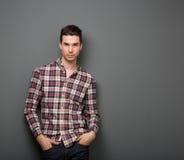 Avkopplad ung man med rutigt posera för skjorta Royaltyfria Bilder