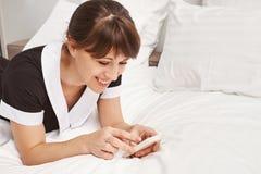 Avkopplade ögonblick på arbete Närbildstående av den positiva husabenägenheten på säng och bläddra eller messaging via smartphone Arkivbilder