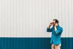 Avkopplade bärande hörlurar för ung man och le lyckligt royaltyfria bilder