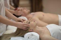 Avkopplade barnpar som får massage i brunnsort Royaltyfri Foto