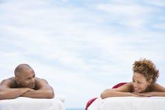 Avkopplade par som ligger på massagetabeller Arkivfoton