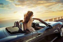 Avkopplade par som rider en cabriolet royaltyfria foton