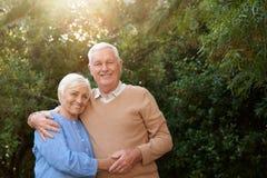 Avkopplade pensionärer som tillsammans står och ler i deras trädgård royaltyfria foton