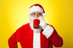 Avkopplade Santa som tycker om hans kopp av kaffe Royaltyfri Fotografi