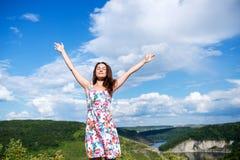 Avkopplade ställningar för en flicka, genom att fördela henne armar framme av horien royaltyfri fotografi