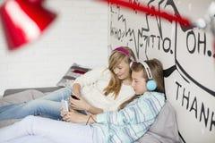 Avkopplade systrar som hemma lyssnar till musik Arkivfoto