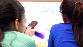 Avkopplade tonårs- flickor med fjärrkontroll som håller ögonen på smart TV lager videofilmer