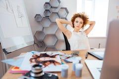 Avkopplat eftertänksamt lockigt fotografsammanträde för ung kvinna på arbetsplats royaltyfria foton