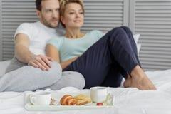 Avkopplat gift par som äter i sovrum Arkivbild