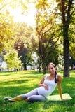 Avkopplat gravid kvinnasammanträde på matt yoga parkerar in Royaltyfria Bilder