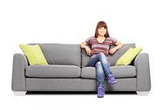 Avkopplat kvinnasammanträde på en modern soffa Royaltyfri Fotografi