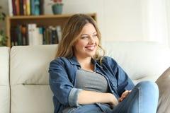 Avkopplat lyckligt kvinnasammanträde på en soffa hemma arkivbild