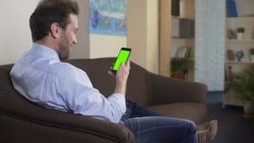 Avkopplat mansammanträde på soffa- och visningfoto i samkväm knyter kontakt på mobiltelefonen arkivfilmer