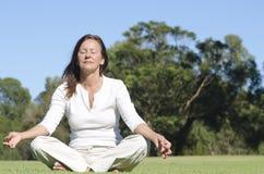 Avkopplat meditera mognar den utomhus- kvinnan Arkivfoto